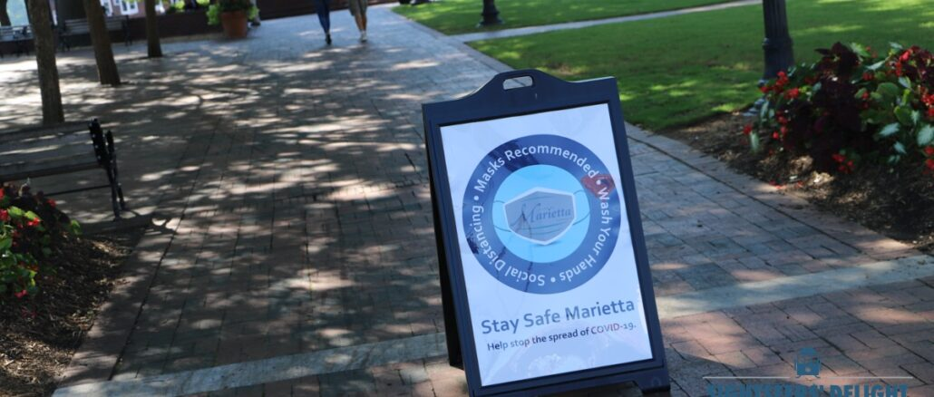 A sign at Glover Park in Marietta, Ga., on Aug. 16, 2020, urges visitors to wear masks and practice social distancing.